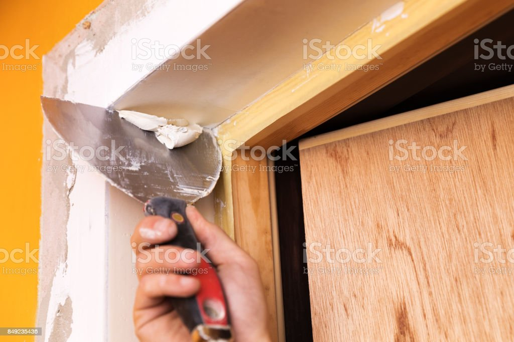 patching plaster around a new door reveals with spatula stock photo