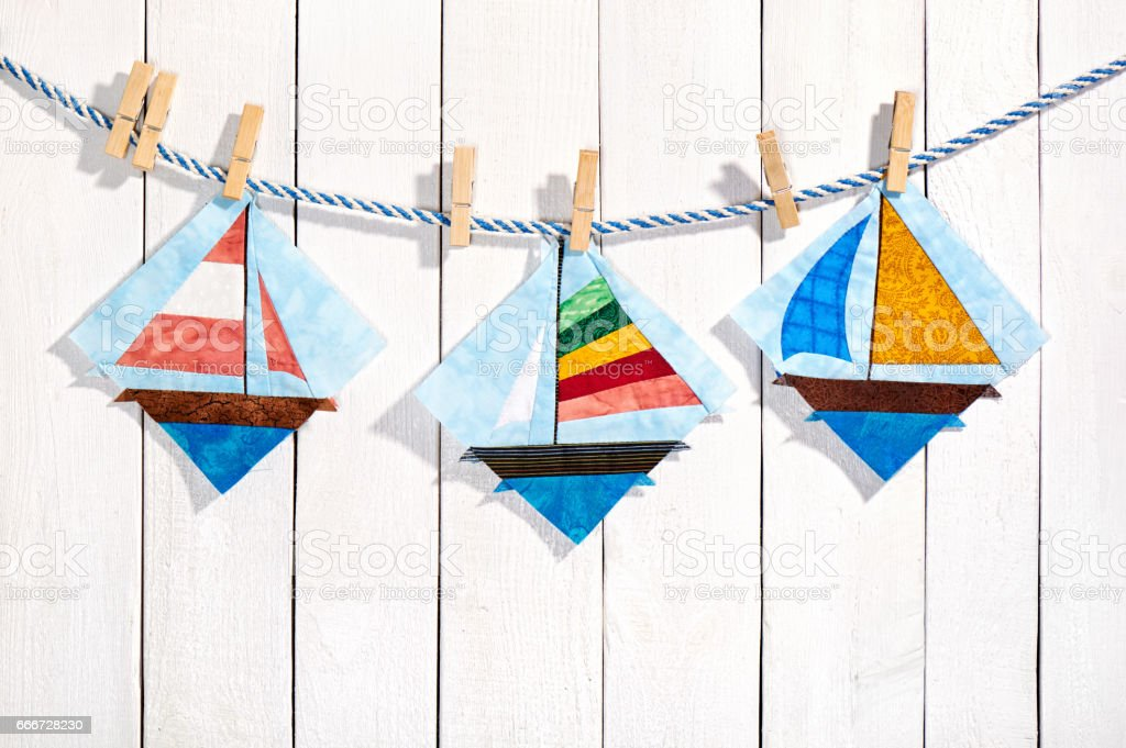 Patchwork blocks attached with clothespins on a rope on a white wooden background stock photo