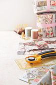 Patchwork blocks, rolls of fabric, sewing accessories on white surface