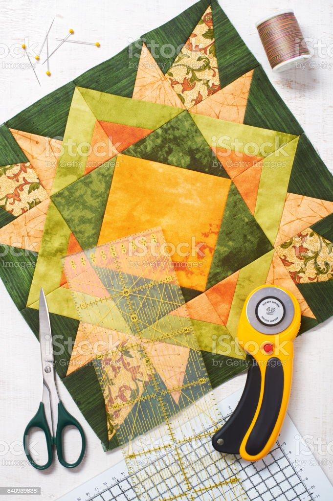 Patchwork orange-green block, quilting fabrics, sewing accessories stock photo