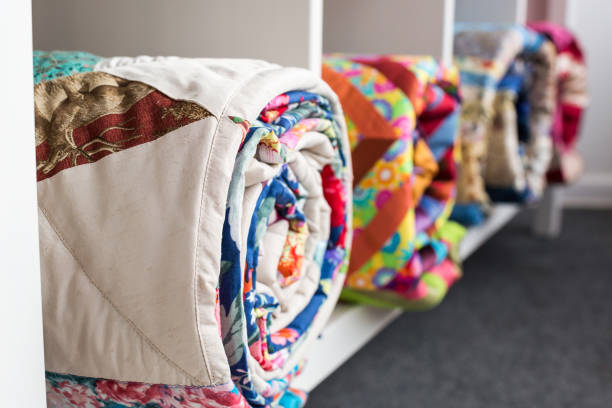 patchwork, sewing and fashion concept - bright finished quilts in the studio at white shelves with three storage compartments, the warehouse of finished products, side view, selective focus - quilt stock photos and pictures