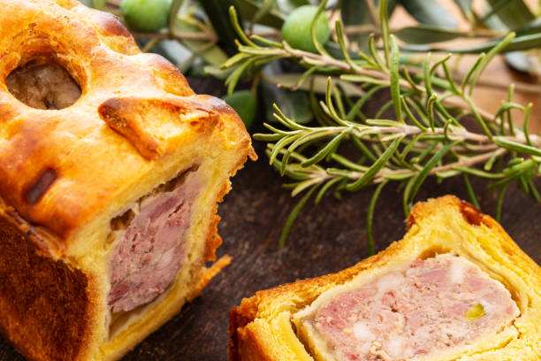 Pate in croute or pie with rosemary twig and green olives on branch with leaves over a dark wooden cutting board and a used oak wood background. stock photo