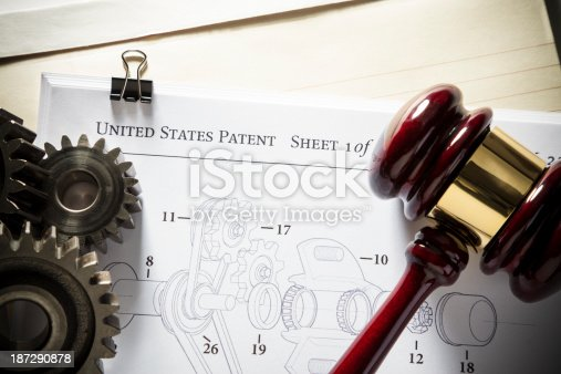 Gavel next to gears and mechanical diagram for patent application.  Concept for patent attorney.