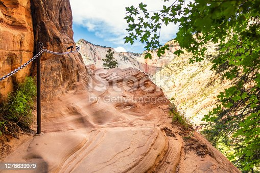 A footpath with a metal chain for added safety on a mountain in Zion National Park, USA.