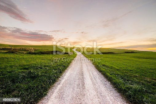 A path in a green hill at sunset