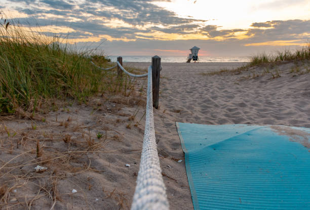 path between roped off sand dunes leading toward the ocean stock photo