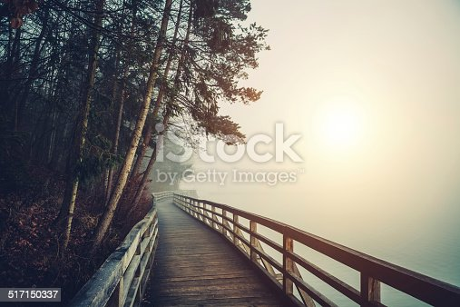 Wooden footpath by the lake on a foggy morning.