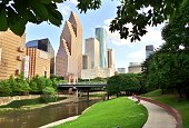 Wide shot of Houston's modern skyline and paved bicycle/walking path in Buffalo Bayou Park on a summer afternoon