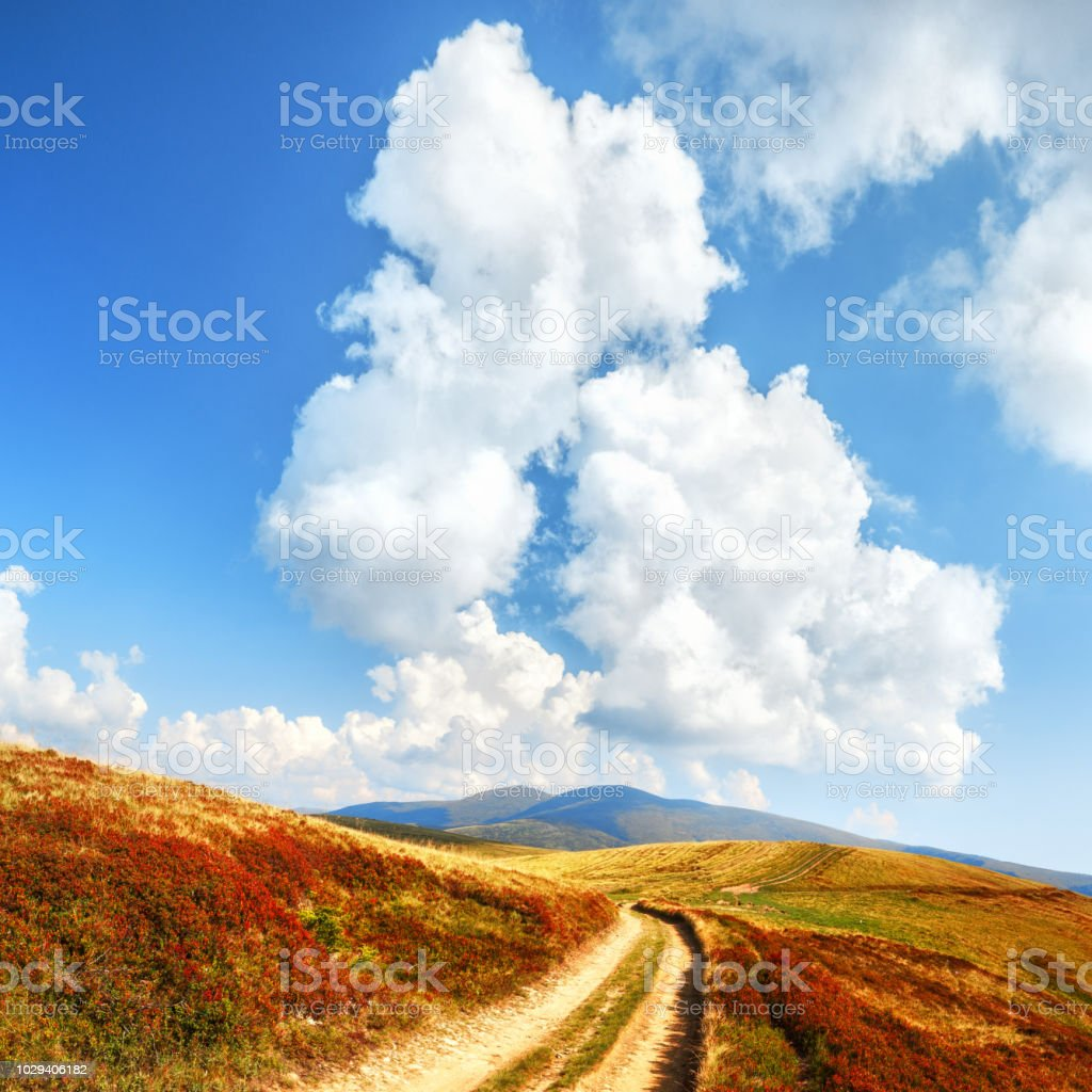 Path in high mountains at background of epic cloudy sky. Boundless...