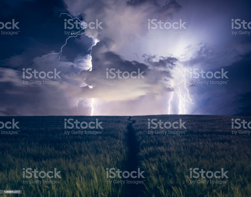 Path Leading Up To A Dramatic Lightning Strike In A Field stock photo