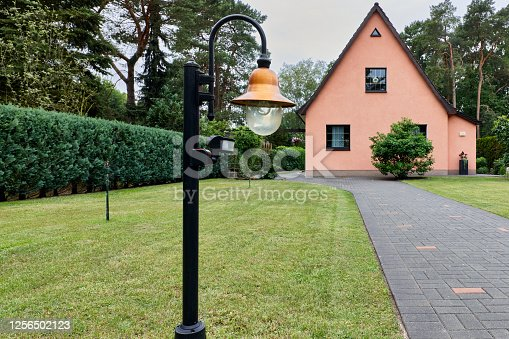 DSLR full frame wide angle view image of a small private house at an overcast morning in Germany with a frontyard with a large meadow and a hedge thuja