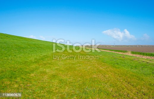Path on a dike in the countryside in sunlight in winter