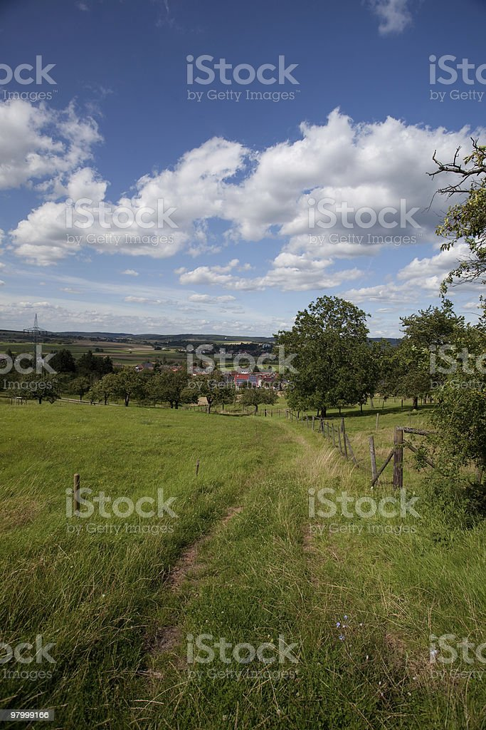 path road small home town welcome blue sky white clouds royalty-free stock photo