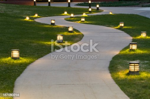 A curving sidewalk lit by small foot lights.