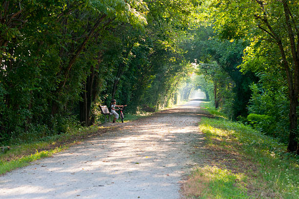 Path Through Tunnel of Trees, Girl with Bike stock photo