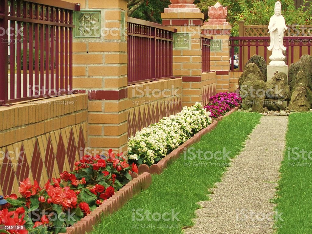 Path to Buddha statue lined with flowers stock photo