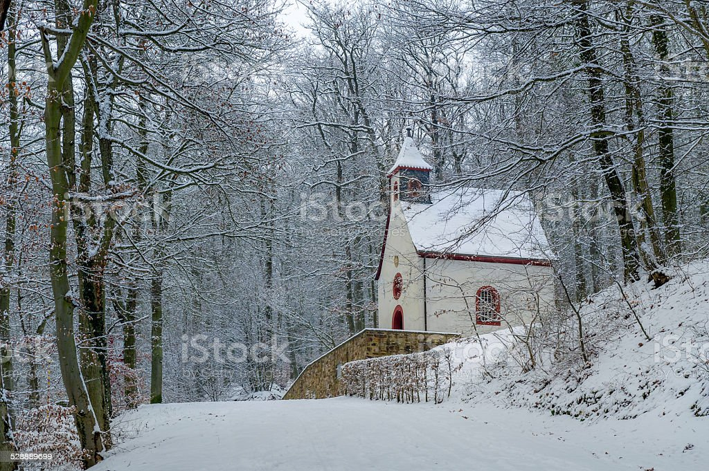 Path to Burg Eltz Small wooden church in winter near the german castle Burg Eltz. Touristic path to castle. Ancient Stock Photo