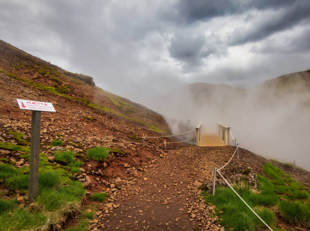path to hot springs with bridge in steam and warning sign in iceland stock photo