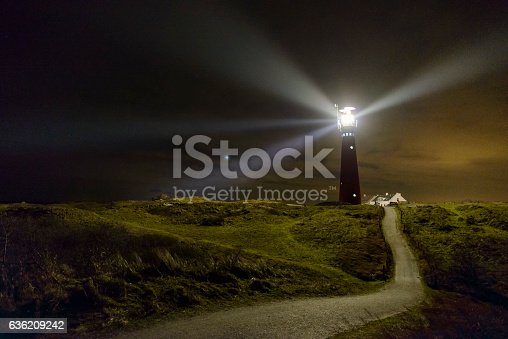 Lighthouse and fishermen's cottages in the night at the island of Schiermonnikoog in the Dutch Waddensea region in the North of The Netherlands. A path is leading up the dunes towards a lighthouse.
