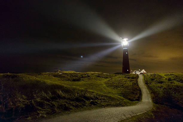 path to the lighthouse in the dunes at night - wegbeleuchtung stock-fotos und bilder