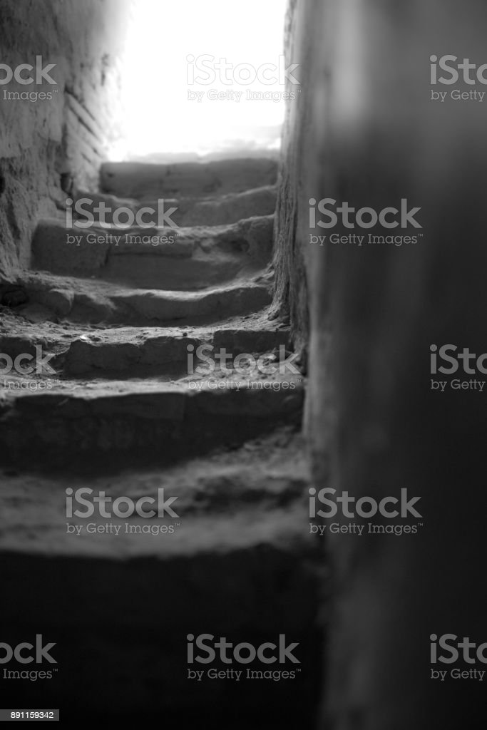 Path up worn stone stairs leading to light at the end of the tunnel stock photo