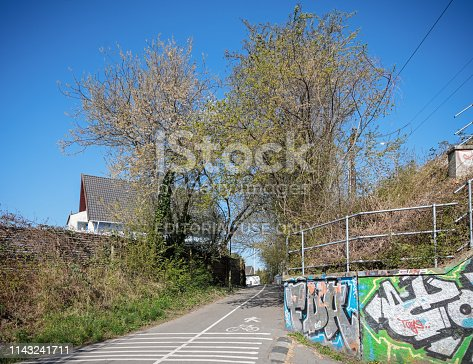 Valby, Copenhagen, Denmark - April 15, 2019: Paths for bikes and pedestrians cover the most of Copenhagen. This is going close to the railroad in a suburban part of the city