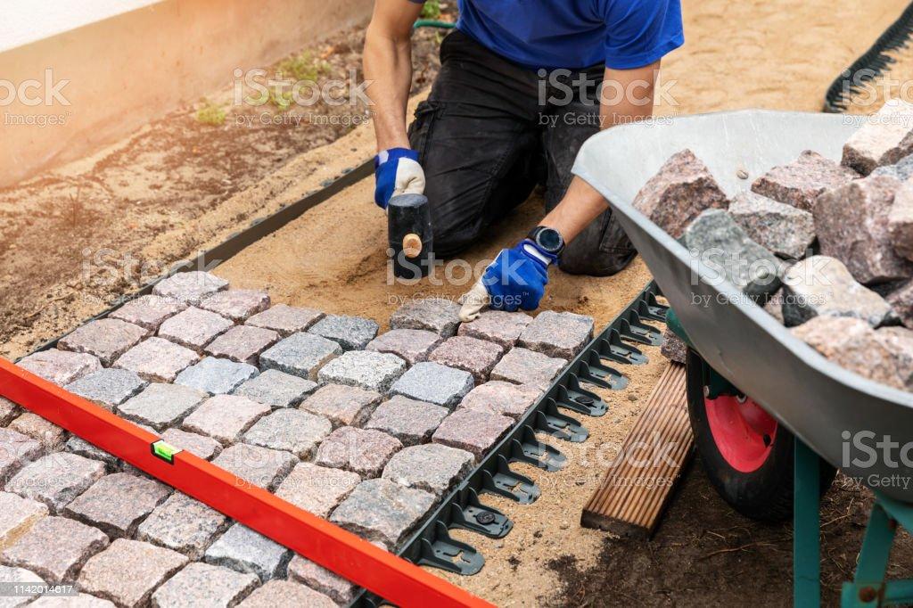 pathway construction - man laying stone pavers at home backyard