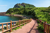 Pathway leading to beach with view over ocean and and volcano crater Ilchulbong, Seongsan, Jeju Island, South Korea