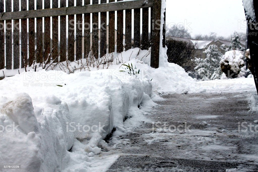 Pathway of cleared snow on residential driveway, UK stock photo