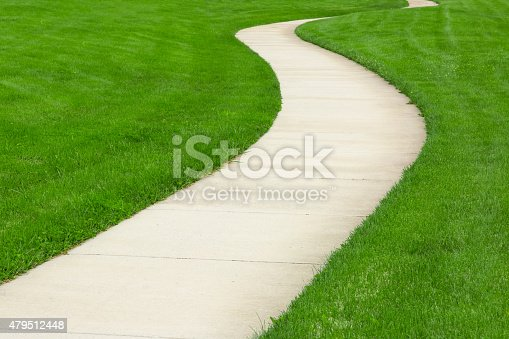 Concrete pathway through green lawn.