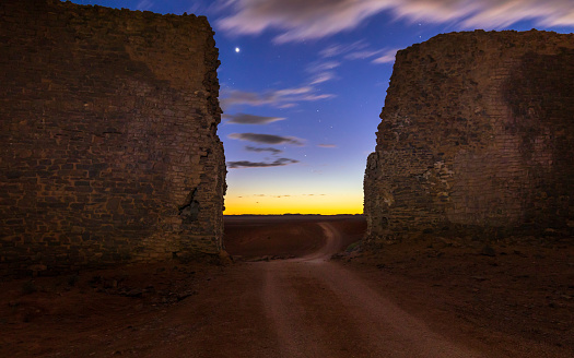 Pathway through ancient brick wall into the desert