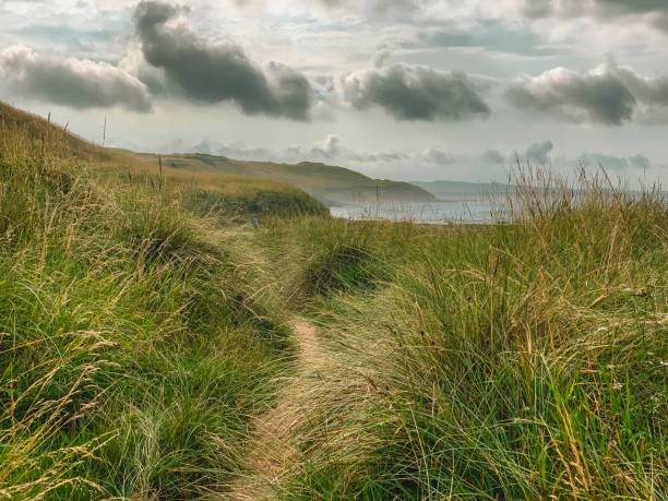 Pathway to the Sea Grassy hill leading down to the coast showing a story sky with clouds. northeastern england stock pictures, royalty-free photos & images
