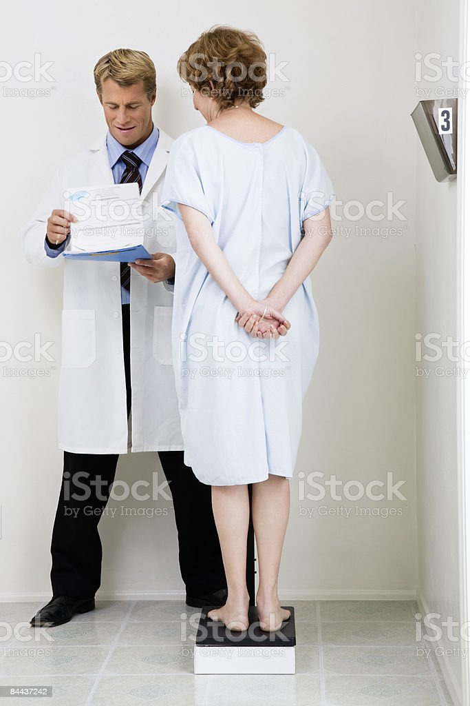 Patient and Doctor at weight scale royalty-free stock photo