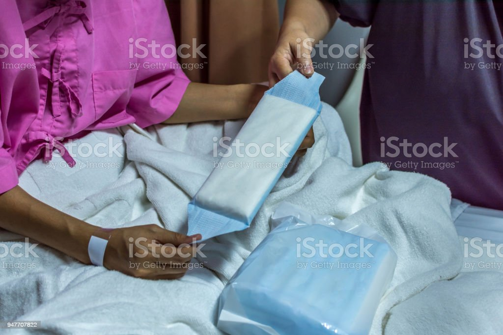 Patient asian woman with adhesive plaster on hand using sanitary napkin for menstruation on patient bed in the hospital stock photo