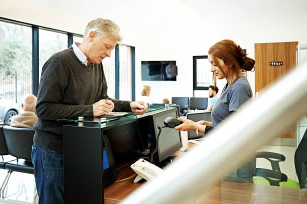 patienten beim zahnarzt zahlen für zahnärztliche behandlung - bürorezeption stock-fotos und bilder