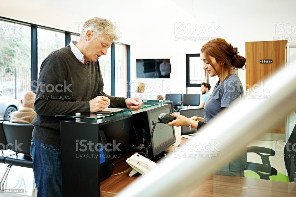 Wonderful Patient At Dentist Paying For Dental Treatment Stock Photo