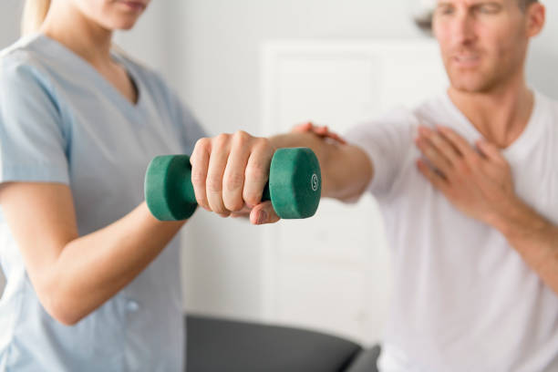 Patient at the physiotherapy doing physical exercises with his therapist A Patient at the physiotherapy doing physical exercises with his therapist sports medicine stock pictures, royalty-free photos & images