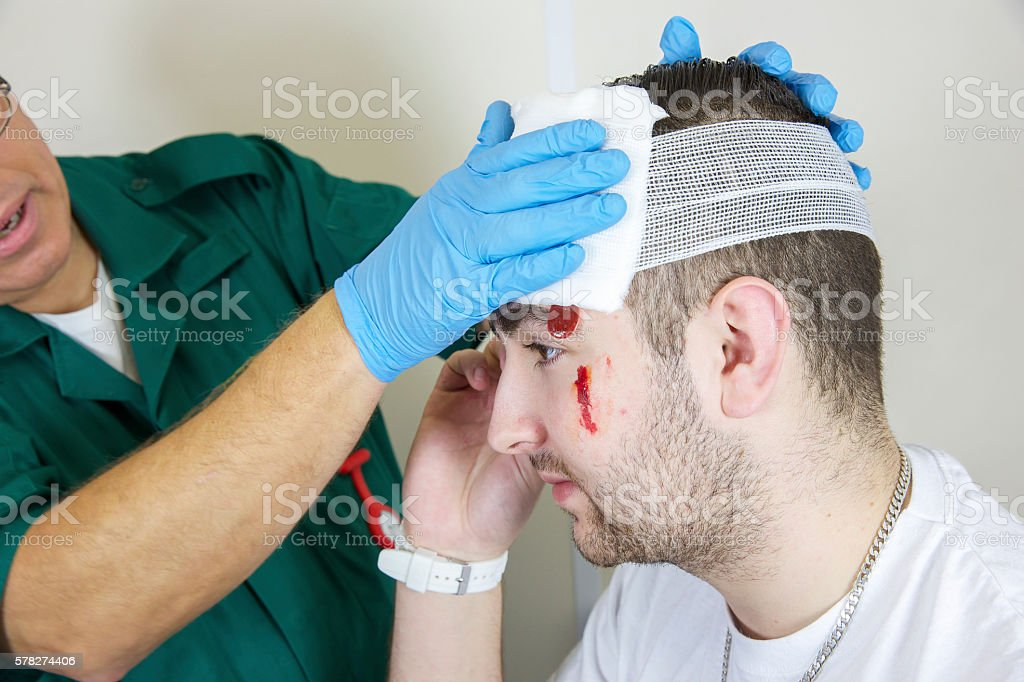 Patient attended to by paramedic nurse after serious head wound stock photo