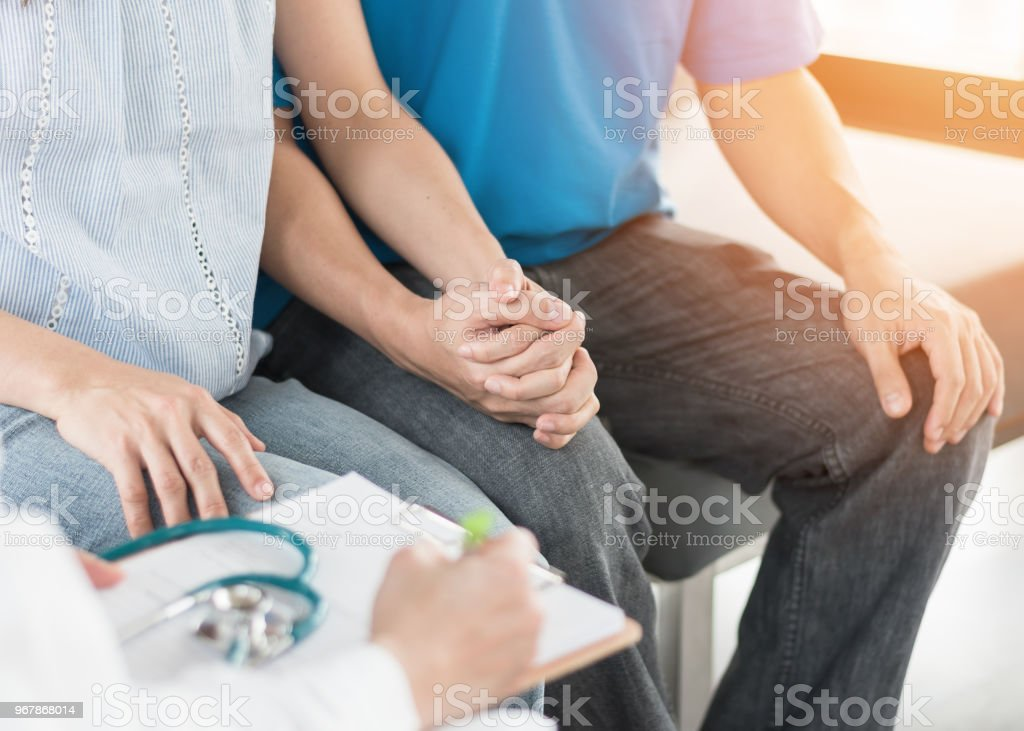 Patient couple having doctor or psychologist consulting on marriage counseling, family medical healthcare therapy, fertility treatment for infertility, or psychotherapy session concept stock photo