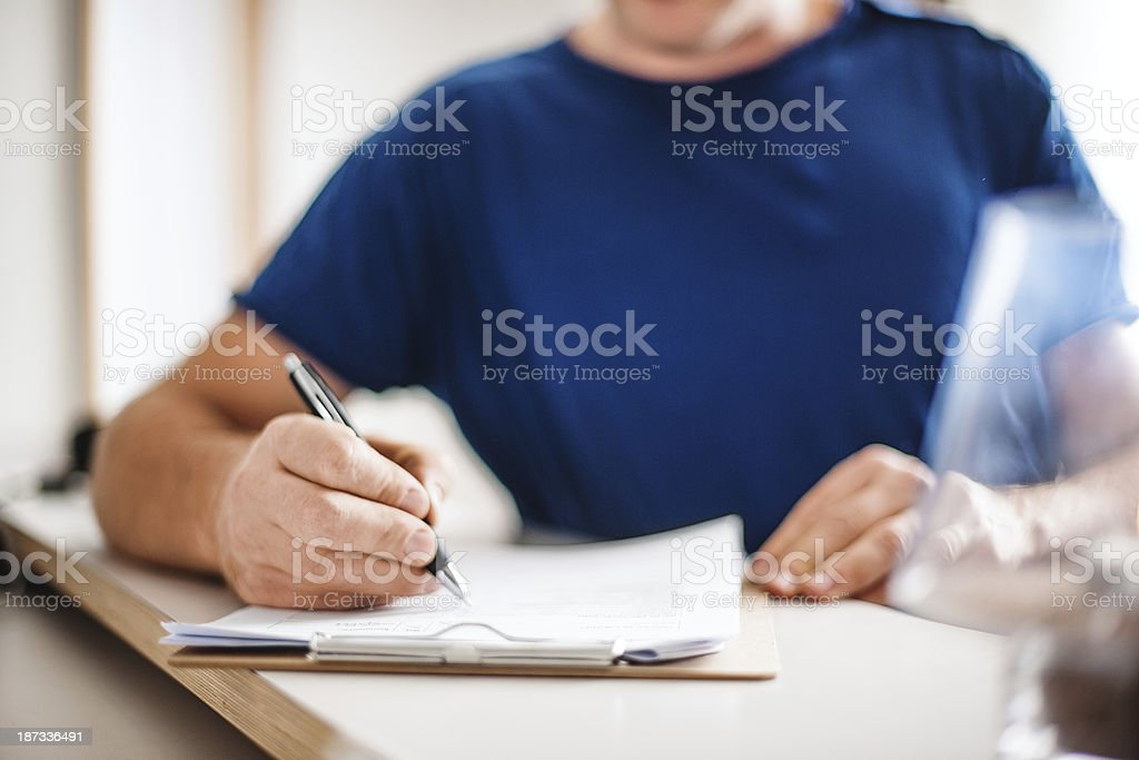 Patient filling in is health declaration at the reception stock photo