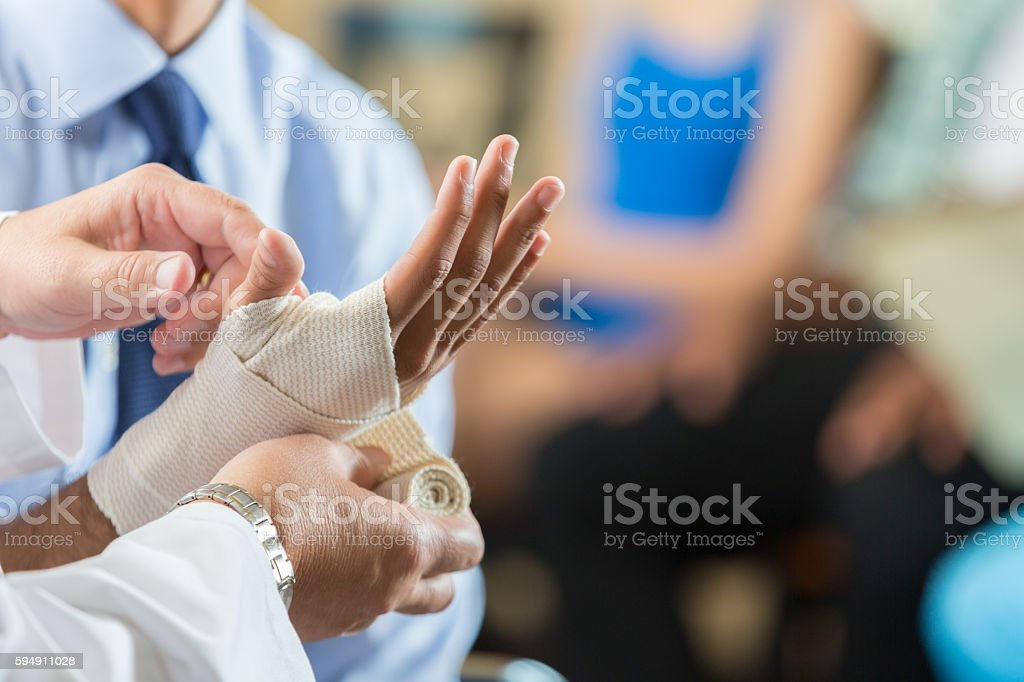 Patient having wrist bandaged by nurse in hospital triage center stock photo