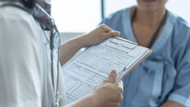 Patient health insurance claim form in doctor or nurse hands for medicare coverage and medical treatment from illness, accident injury and admitted in hospital ward stock photo