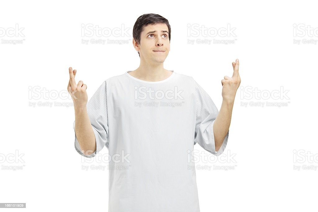 Patient in a hospital gown with fingers crossed royalty-free stock photo