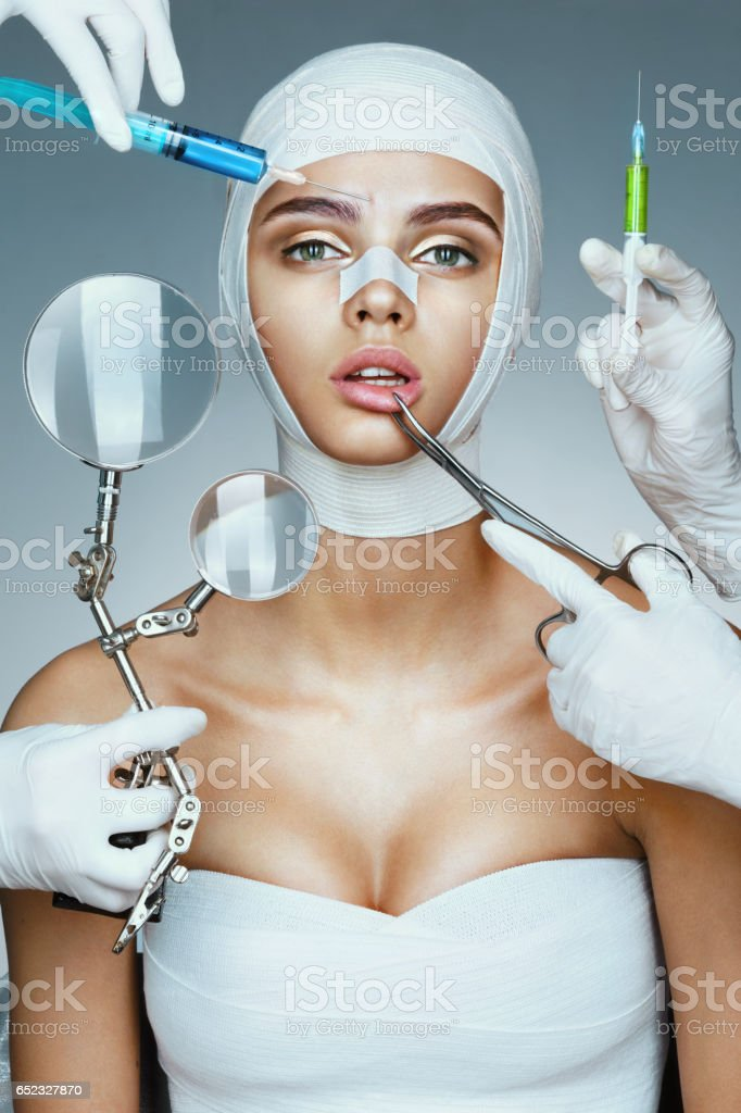 Patient in bandages and many hands holding medical instruments. stock photo
