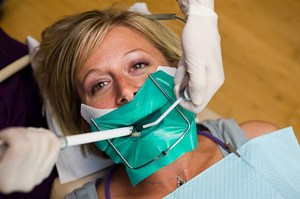 patient in dental chair getting a cavity filled - zuigslang stockfoto's en -beelden