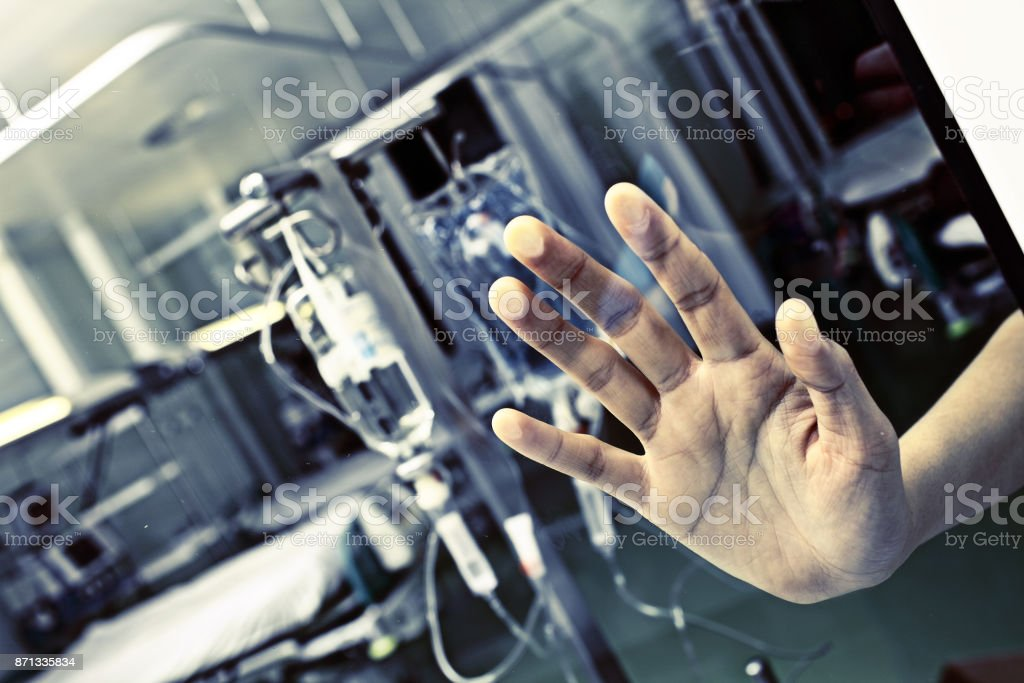 Patient in hospital pressed his hand to the glass stock photo