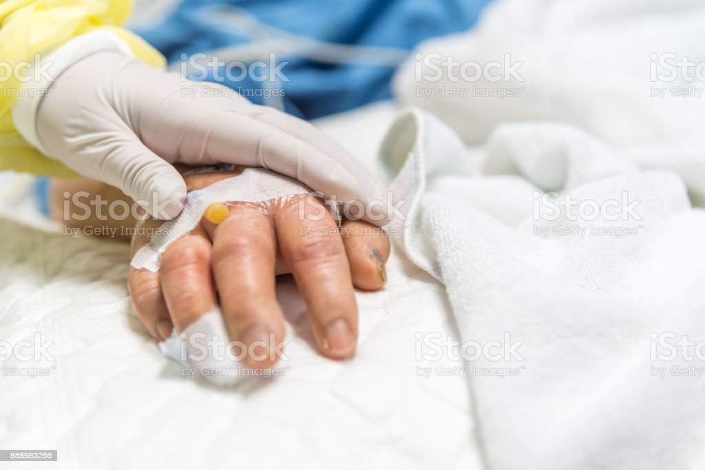 Patient in the hospital with saline intravenous and relatives patient hand holding a elderly patient hand stock photo