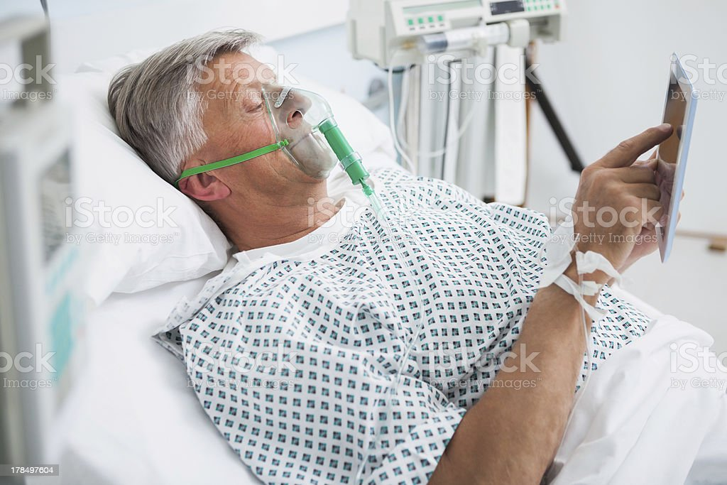 Patient is lying on bed reading in hospital ward stock photo
