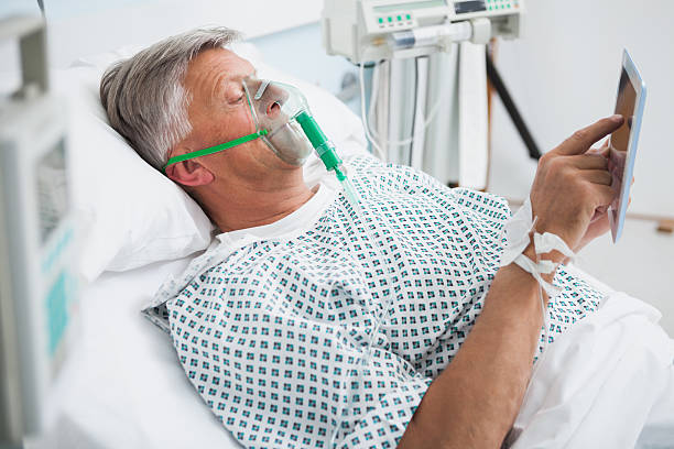 Patient is lying on bed reading in hospital ward Patient is lying in bed reading wearing an oxygen mask in hospital ward oxygen mask stock pictures, royalty-free photos & images