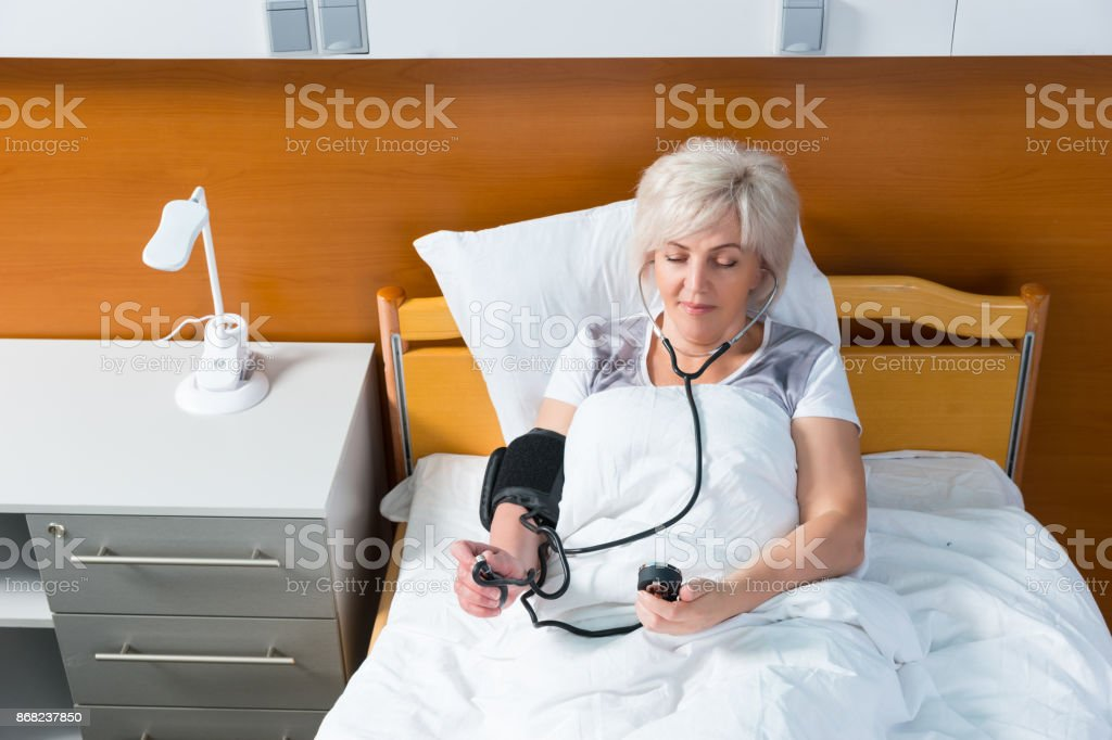 Patient is measuring the arterial pressure using a medical equipment, while lying in the hospital bed stock photo
